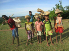Malagasy children transporting building supplies on foot